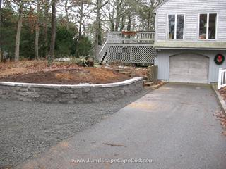 Driveway expansion with stone retaining block wall.